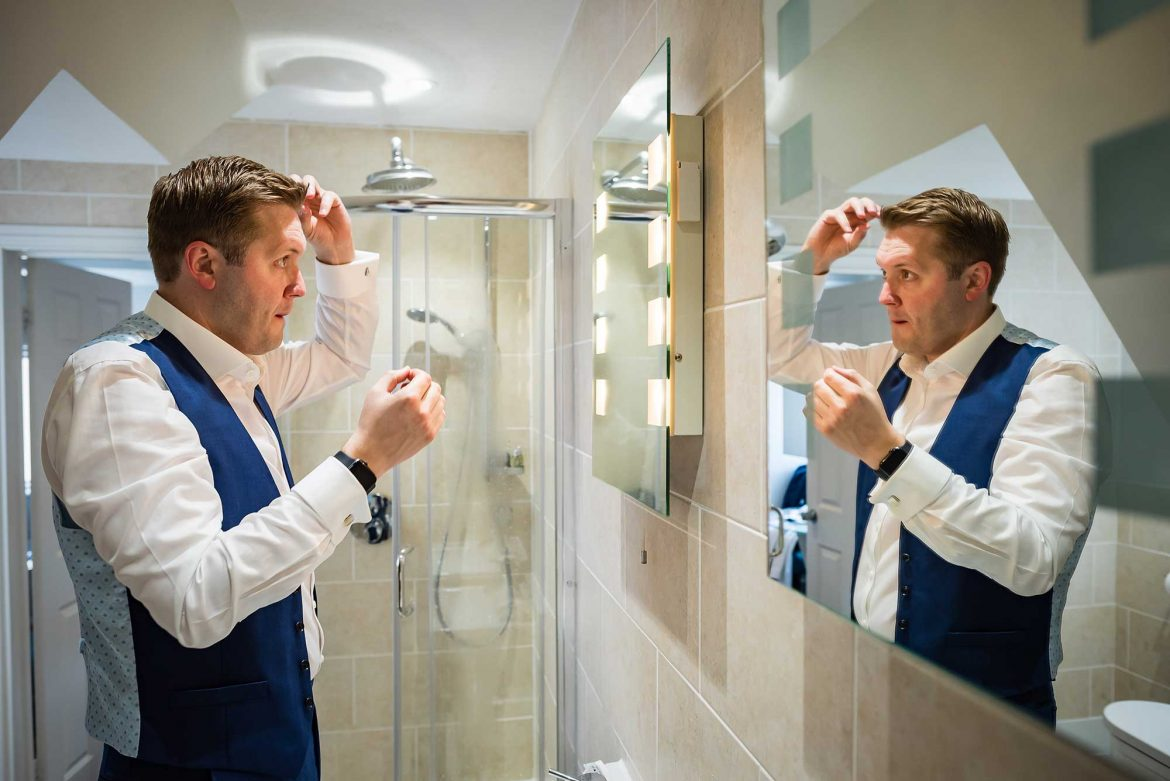 groom looks in mirror and does hair