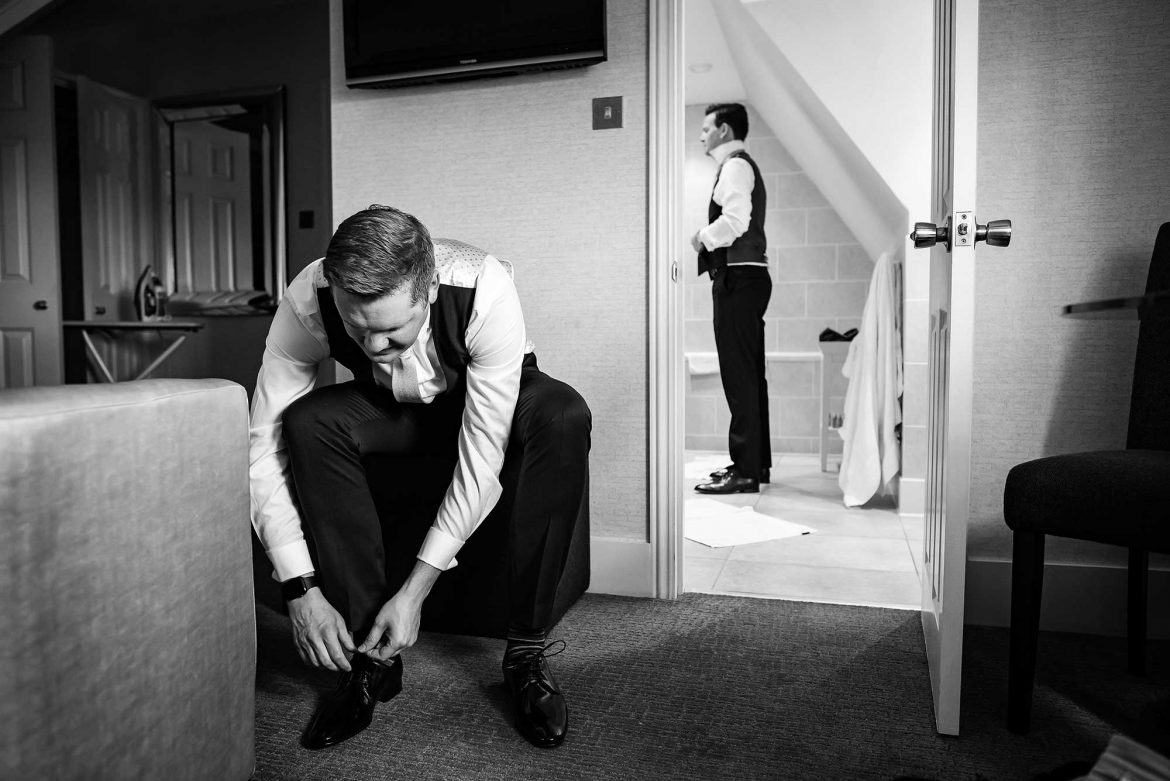 groom puts on shoes while best man adjusts waistcoat