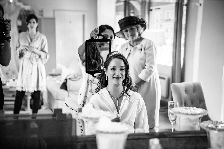 bride looks at hair in mirror
