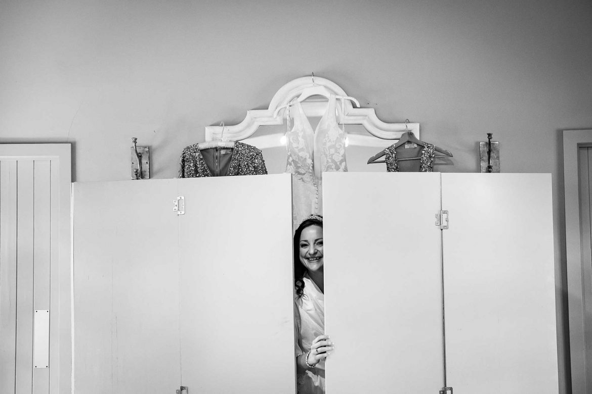 bride peaks out from behind her dressing area
