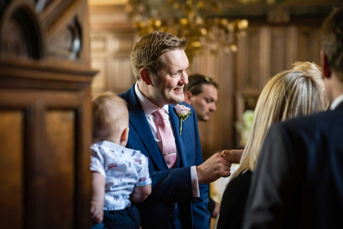groom shakes hands with baby