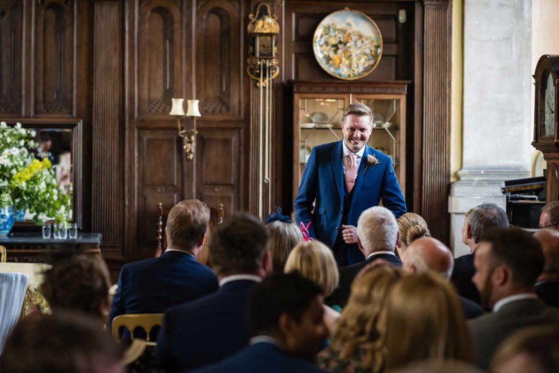 groom smiles at guests