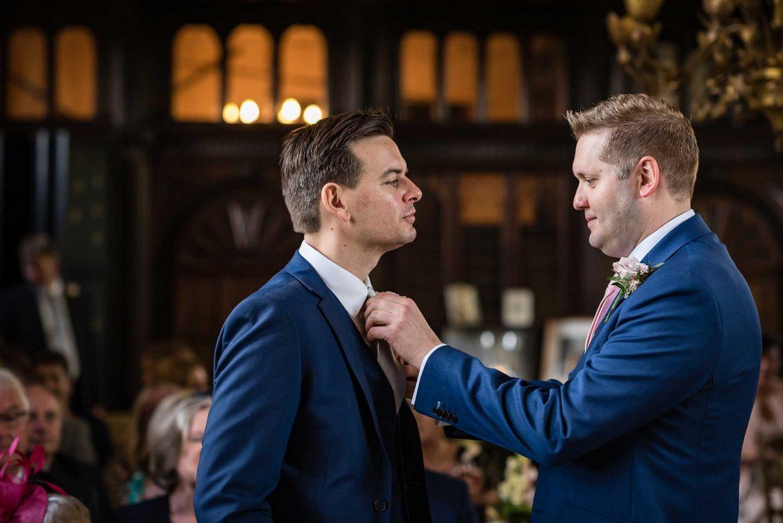groom helps best man with tie