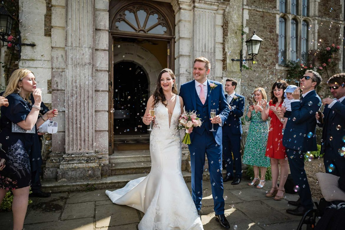 bride and groom with bubbles at Loseley Park Wedding