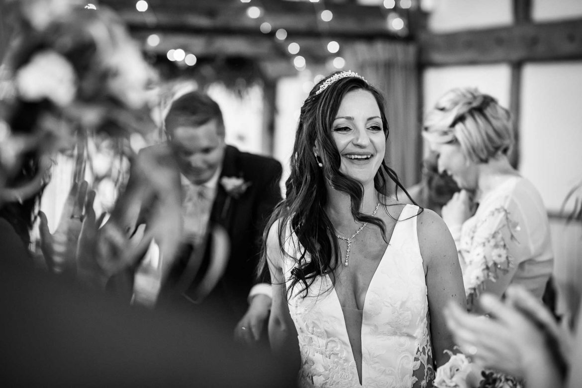 bride smiling as she walks into Loseley Park Wedding