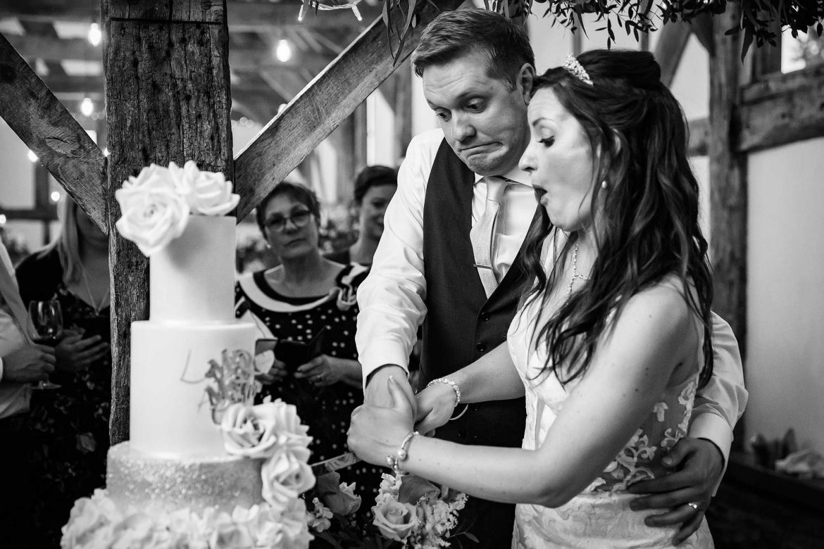 bride and groom cut cake at Loseley Park Wedding